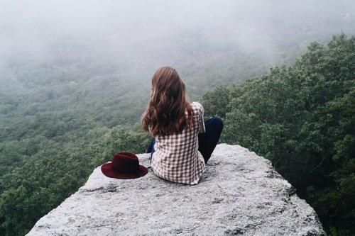 岩場に座る女性の後ろ姿