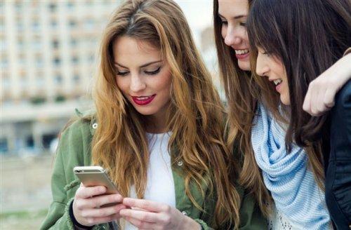 携帯を見ている3人の女性