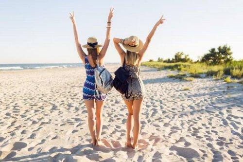 両手を上げて砂浜を歩く女性2人