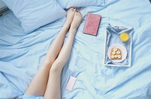 ベッドに座る女性の脚