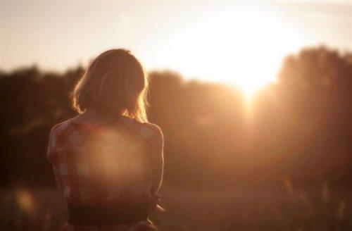 夕日と背中を見せている女性