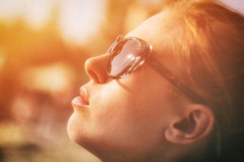 夕日を見るサングラスをかけた女性