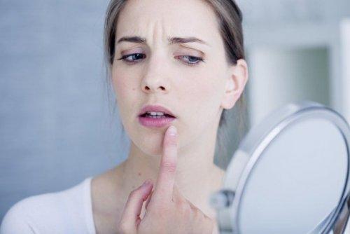 唇のできものを手鏡で見る女性
