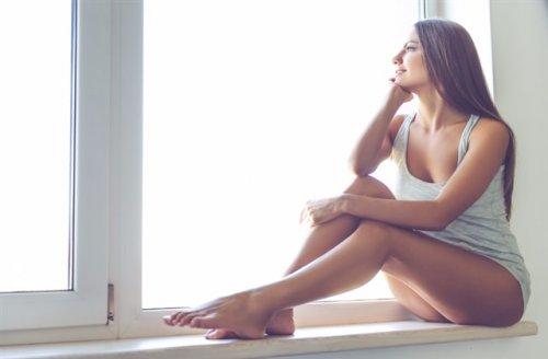 窓辺に座ってい頬杖をついている女性