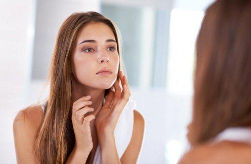 鏡で自分の顔を見つめている女性
