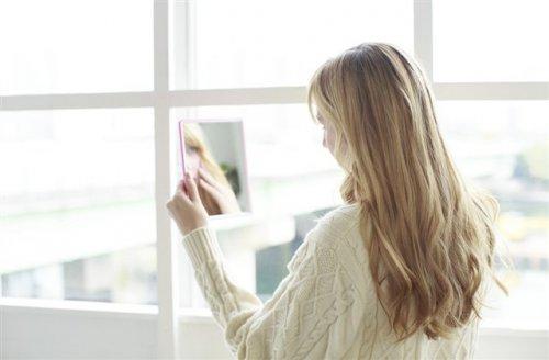窓辺で鏡を見ている女性