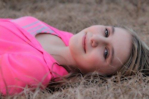 野に横たわって微笑む女性