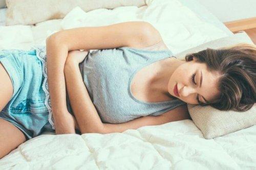 お腹を抱え寝転ぶ女性