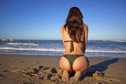 ビキニ姿で砂浜に座る女性