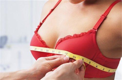 バストのサイズを測っている赤いブラの女性