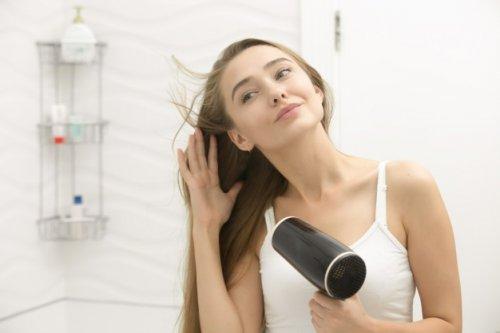 鏡に向かってドライヤーをする女性