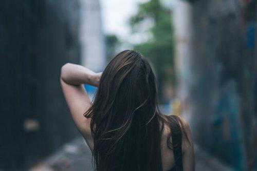 髪を気にする女性の後ろ姿