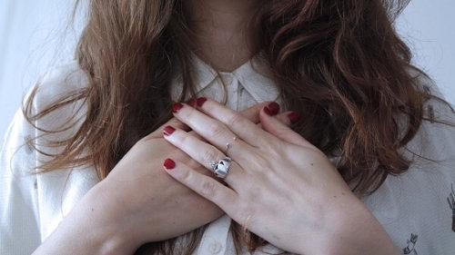 胸の前で手を重ねる女性