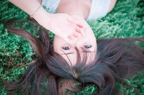 草むらで寝そべる女性